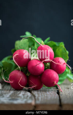 Branch of fresh radish over rustic old boards. The concept of a harvest and organic food. Copy space. - Stock Photo