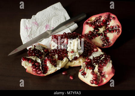 Cut open pomegranate with stainless steel knife & paper towel on dark timber background - with copy space - Stock Photo