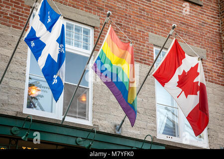 Three flags hanging in Quebec City. Canadian, Quebec Provincial, and the Rainbow Fag. - Stock Photo