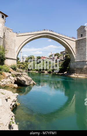 Mostar, Bosnia and Herzegowina, July 15 2017: Historic arch bridge over the neretva river in Mostar on a beautiful - Stock Photo