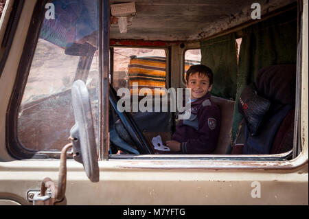 Young Bedouin boy seated in a old Toyota four wheel drive in the Wadi Rum area in Jordan. - Stock Photo