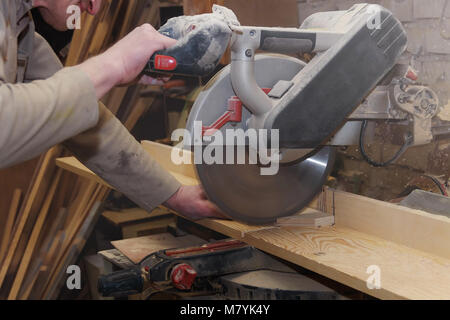 Carpenter Working on Woodworking Machines in Carpentry Shop. Male Hand Close up. - Stock Photo