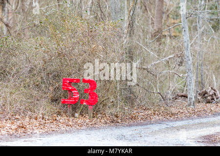 the number 53 in bright red on the side of the road serving as a house number - Stock Photo