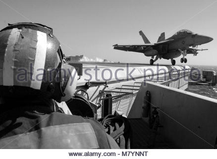 McDonnell Douglas FA-18F Super Hornet attached to Strike Fighter Squadron. A U.S. Sailor mans a catapult operating - Stock Photo