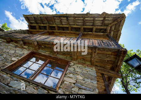 Window cloud reflections old stone and wood house - Stock Photo