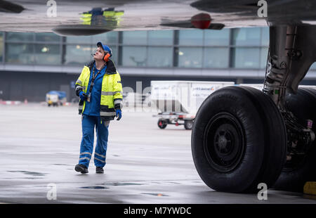 08 March 2018, Germany, Frankfurt: Sabrina Boock, in charge of ground handling operations, inspects the underbody - Stock Photo