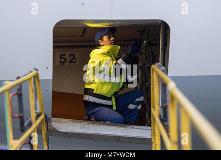 08 March 2018, Germany, Frankfurt: Sevim Sejdijaj, in charge of ground handling operations,  kneels inside the - Stock Photo
