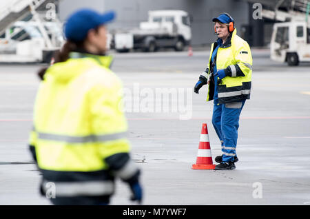 08 March 2018, Germany, Frankfurt: Sevim Sejdijaj, in charge of ground handling operations, places pylons on the - Stock Photo