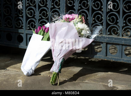 Cambridge, Britain. 14th Mar, 2018. Flowers are seen at the gate of Gonville and Caius College at the University - Stock Photo