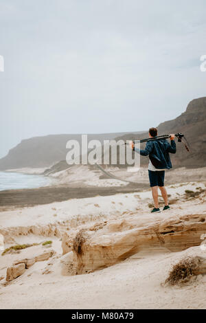 Photographer with camera looking for motive of unique landscape. Sand dunes and volcanic cliffs on the Atlantic - Stock Photo