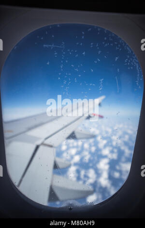 Clouds and sky as seen through window of an aircraft. Small ice crystals on the window - Stock Photo