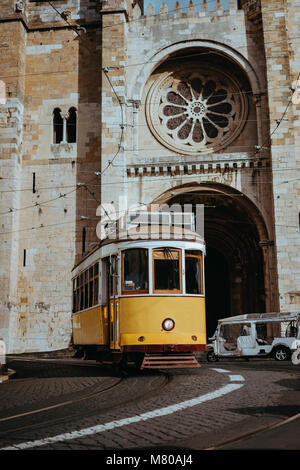 Quaint yellow tram passes directly in front of the Se Cathedral in Lisbon. Lisboa Lissabon - Stock Photo