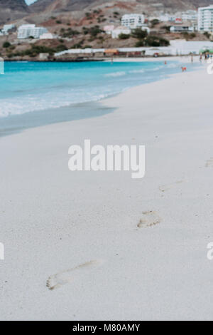 Ocean waves rolling to the foot prints on the tropical beach with azure water - Stock Photo