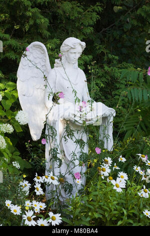 Female angel statue in a landscaped residential backyard garden in summer. - Stock Photo