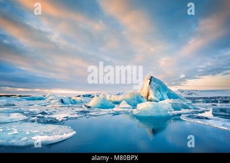 Icebergs float on Jokulsarlon glacier lagoon at sunrise, in Iceland. - Stock Photo