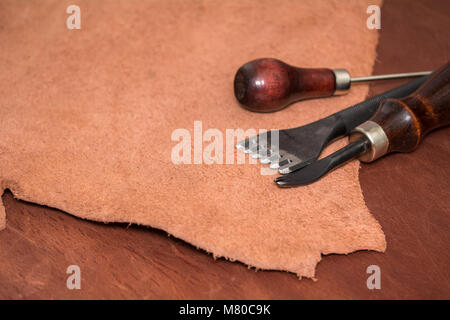 Tools for leather crafting and pieces of brown leather. Manufacture of leather goods. - Stock Photo