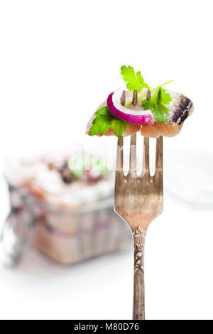 sliced  salted herring on vintage fork - Stock Photo