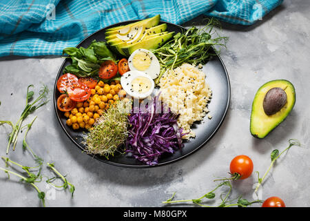 Healthy vegan lunch bowl. Vegan buddha bowl. Vegetables and nuts in buddha bowl on concrete background. - Stock Photo