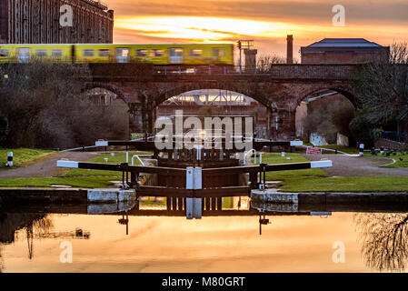 Merseyrail Electric train passing over the Leeds Liverpool canal locks at Stanley Dock. Evening light. Sunset - Stock Photo