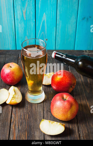 Glass of cider with apples and bottle on rustic wooden background. - Stock Photo