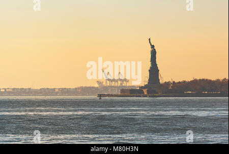 Sunset over the Statue of Liberty in New York - Stock Photo