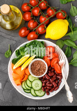 Vegetarian buddha bowl. Raw vegetables - tomatoes, cucumbers, beans, spinach, carrots, lemon and flax seed in a - Stock Photo