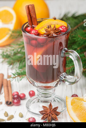Mulled wine hot drink with cranberry, citrus, cinnamon, cardamom and star anise in a glass on the table. Christmas. - Stock Photo