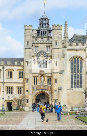 Tourists by the clock tower in the Great Court at Trinity college, Cambridge University, England, on a sunny winter - Stock Photo