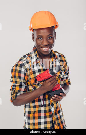 African American worker uses electric screwdriver - Stock Photo