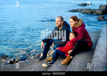 family mom, dad and son are sitting on the beach by the sea and looking into the distance. Season - spring, autumn. - Stock Photo