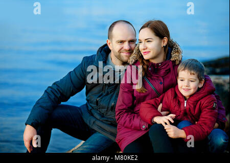 family mom, dad and son sitting on the beach by the sea. Season - spring, autumn. The concept of family happiness - Stock Photo