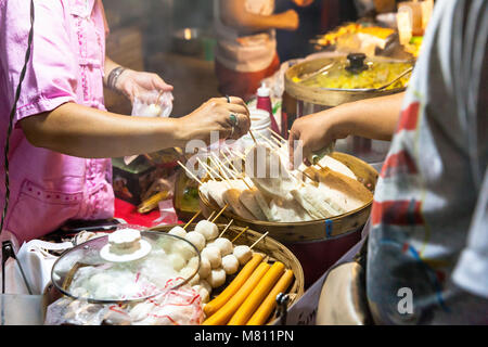CHIANG MAI, THAILAND - AUGUST 21: Man buys street food at the Sunday Market (Walking Street) on August 21, 2016 - Stock Photo