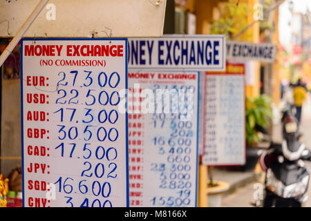 Signs with exchange rates outside a bureau de change money exchange in Hoi An, Vietnam - Stock Photo