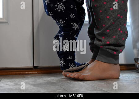 baby stands on mothers feet - Stock Photo