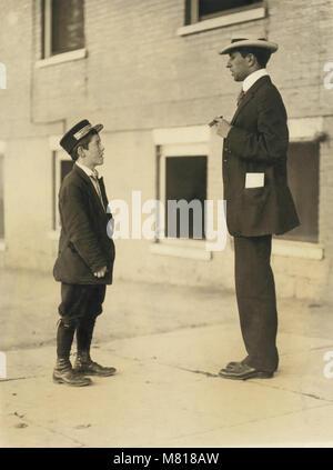 A.D.T. Boy, 13 years, Portrait Standing Facing Man, Burlington, Vermont, USA, Lewis Hine for National Child Labor - Stock Photo