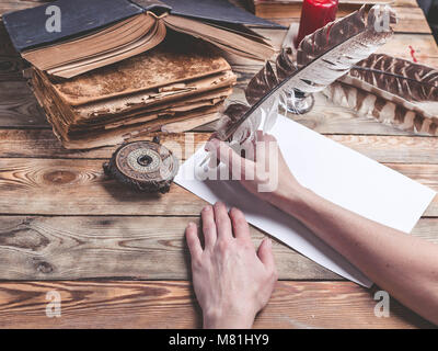 The female hand writes the letter with feather quill pen. Old books, compass on a wooden background. Retro style - Stock Photo