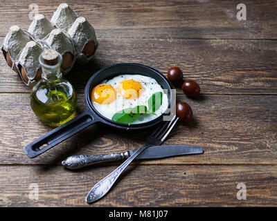 The pan fried eggs, cherry tomatoes and fresh spinach. Concept of a healthy breakfast. - Stock Photo