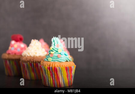home baked cupcakes with colorful frosting and fruit - Stock Photo