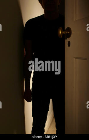 Silhouette of a man standing in doorway with a clenched fist. Domestic violence. - Stock Photo