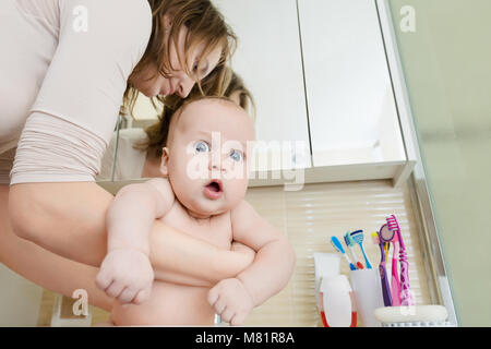 Portrait of surprised infant boy in bathroom. Mother wahing baby in washbasin. Child with fun amazed face expression - Stock Photo