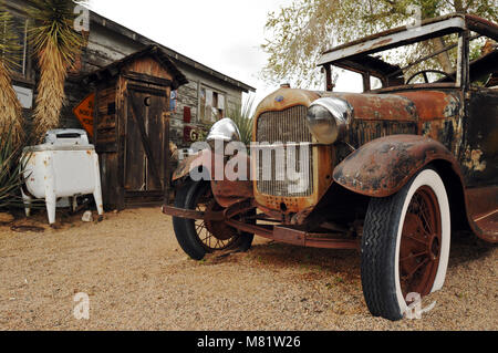 An outhouse and a rusty old Ford automobile are part of the display at the Hackberry General Store in Arizona, a - Stock Photo