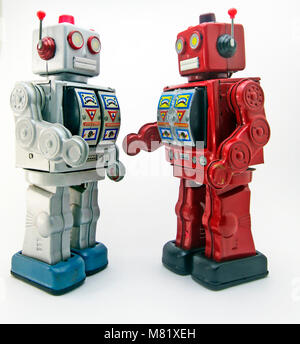 two retro robots meet and shake hands - Stock Photo