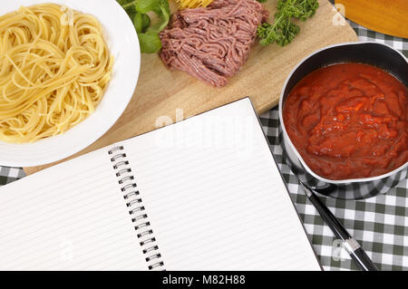 Making Italian spaghetti bolognese with ingredients and blank recipe book or cookbook. Space for copy. - Stock Photo