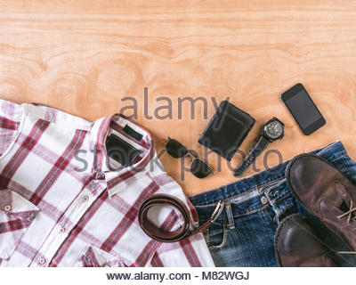 Top view of Men's casual outfits with accessories on wooden table background - Stock Photo