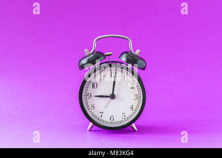 Black modern alarm clock set at nine o'clock, isolated, work school begins concept, ultraviolet background - Stock Photo