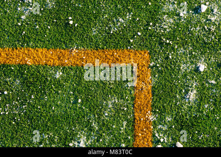Green grass on a football soccer field covered with a snow - Stock Photo