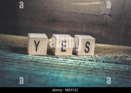 Macro Of The Word Yes Formed By Wooden Blocks On A Wooden Floor - Stock Photo