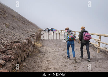 Surrounded by cloud tourists walk up the trail leading to the summit of Mount Vesuvius, Bay of Naples, Italy. - Stock Photo