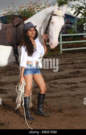 Girl with long hair wearing short pants with horse - Stock Photo
