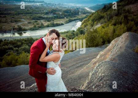 Sensitive portrait of the adorable newlywed couple hugging at the background of the magnificent landscape during - Stock Photo